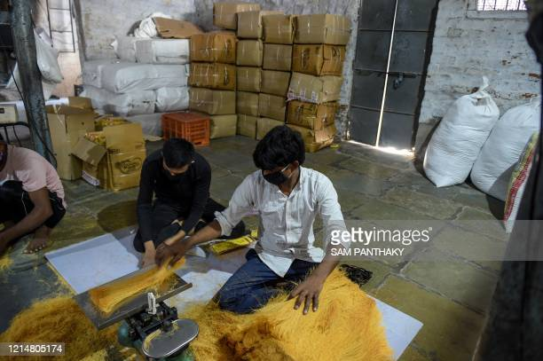 Labourers wearing facemasks weigh vermicelli before packing at a workshop in Ahmedabad on May 23, 2020.