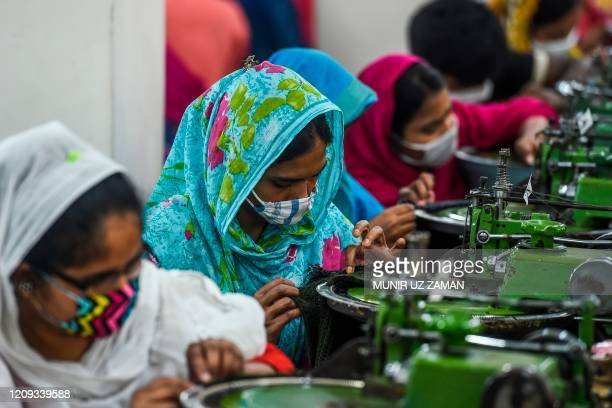 Labourers wearing facemasks work in a garment factory during a government-imposed lockdown as a preventative measure against the COVID-19 coronavirus...