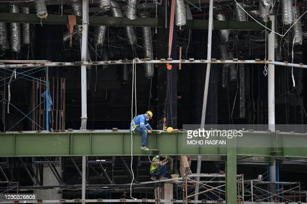 Labourers work at a construction site in downtown Kuala Lumpur on December 28, 2020.