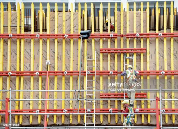 Labourers work at a construction site of an office building in Singapore on October 30 2013 The Monetary Authority of Singapore on October 30 said...