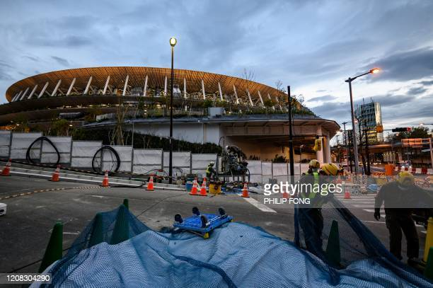 Labourers work at a site near the Japan National Stadium in Tokyo on March 27 three days after the historic decision to postpone the 2020 Tokyo...