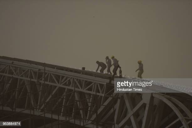 Labourers work at Noida stadium amid a sudden heavy dust storm on May 2 2018 in Noida India A squall and dust storm followed by heavy rain lashed the...
