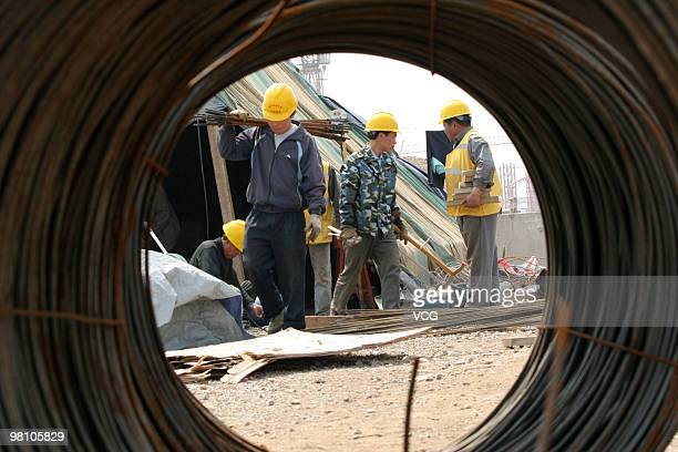 Labourers work at the construction site of the Nanjing South Station of BeijingShanghai Highspeed Railway on March 28 2010 in Nanjing Jiangsu...