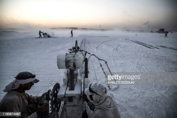TOPSHOT Labourers work at the White Mountain limestone extraction quarry site near Egypt's southern city of Minya some 265 kilometres south of the...