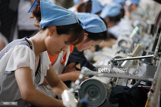 Labourers work in a clothing factory in Huaibei, north China's Anhui province on May 23, 2013. Manufacturing activity in China contracted in May for...