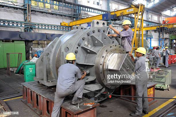 Labourers work on heavy machinery at the Elecon Engineering Company Limited factory in Vallabh Vidyanagar some 90 kms from Ahmedabad on October 28...