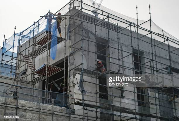 Labourers work on the ongoing construction of the mass rapid transit project in Jakarta on July 14 ahead of the upcoming Asian Games Indonesia will...