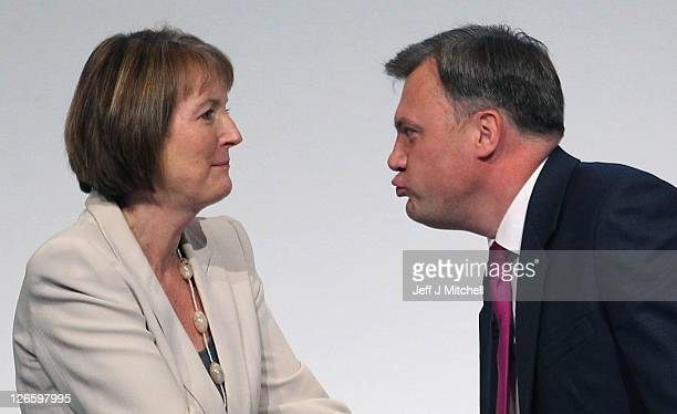 Labour's Shadow Chancellor Ed Balls leans over to kiss deputy party leader Harriet Harman as he receives applause from Ed Miliband leader of the...