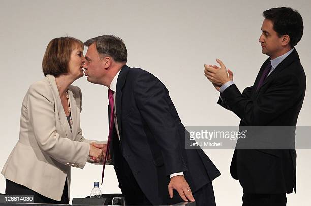 Labour's Shadow Chancellor Ed Balls leans over to kiss deputy party leader Harriet Harman as Labour Party leader Ed Miliband looks on after...