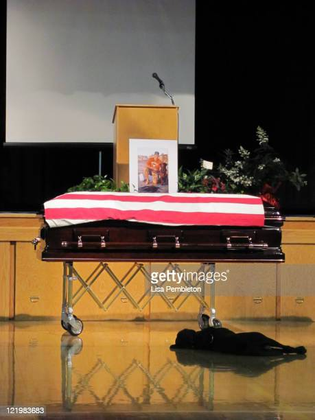 Labrador retriever Hawkeye lays by the casket during the funeral of his owner Navy SEAL Jon Tumilson at the RuddRockfordMarble Rock Community School...