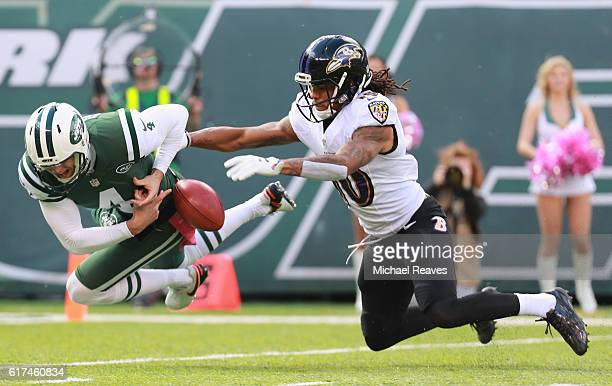 Lac Edwards of the New York Jets fumbles the ball against Chris Moore of the Baltimore Ravens in the first quarter at MetLife Stadium on October 23...