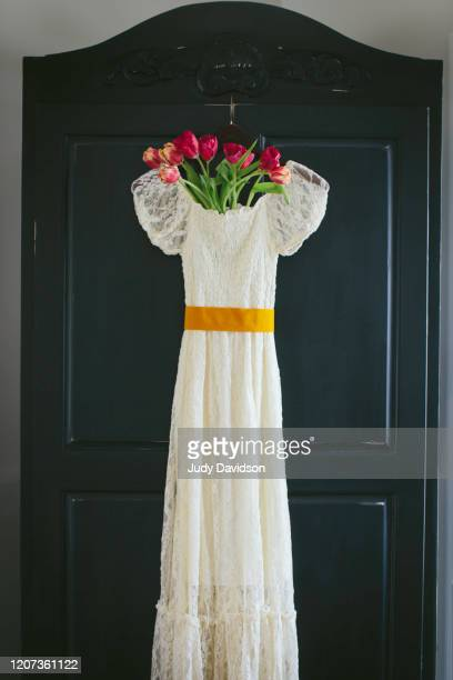 lace dress hanging on armoire with tulips - evening gown stock pictures, royalty-free photos & images
