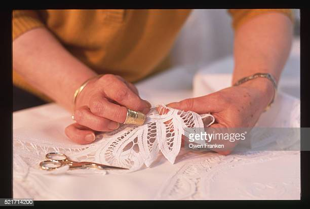 lacemaker attaching lace to a tablecloth - lacemaking stock pictures, royalty-free photos & images