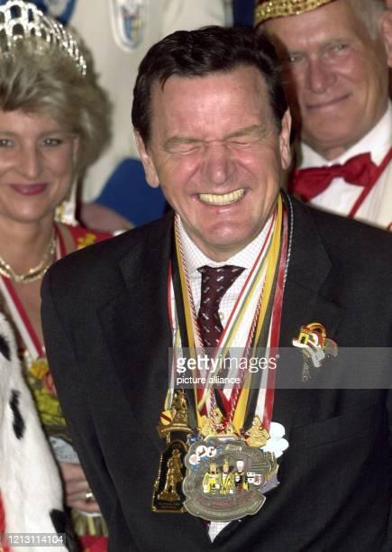 """Lachend """"erträgt"""" Bundeskanzler Gerhard Schröder am 1.3.2000 beim Karnevalsempfang im Bonner Kanzleramt die Last der ihm verliehenen Karnevalsorden...."""