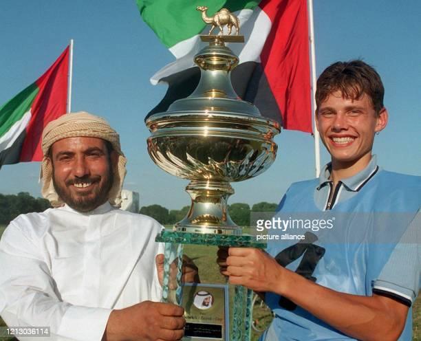 Lachend halten am 17.8.1997 auf der Galopp-Rennbahn Hoppegarten bei Berlin der Sieger des Kamelrennens um den Scheich-Said-Cup, der deutsche Jockey...