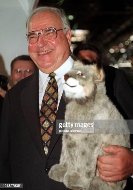 Lachend hält Bundeskanzler Helmut Kohl am 1.9.1997 während eines Eröffnungs-Rundgangs zur Einkaufsmesse Ost in Düsseldorf einen Stoff-Luchs im Arm....