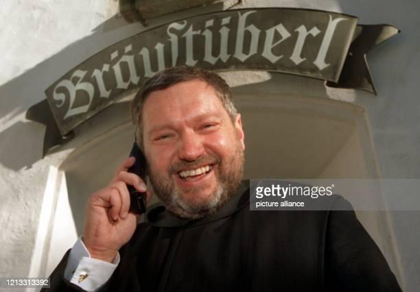 """Lachend telefoniert Pater Anselm Bilgri vom Kloster Andechs am 16.1.1997 vor dem berühmten Bräustüberl auf dem """"Heiligen Berg"""" mit seinem Handy. Er..."""