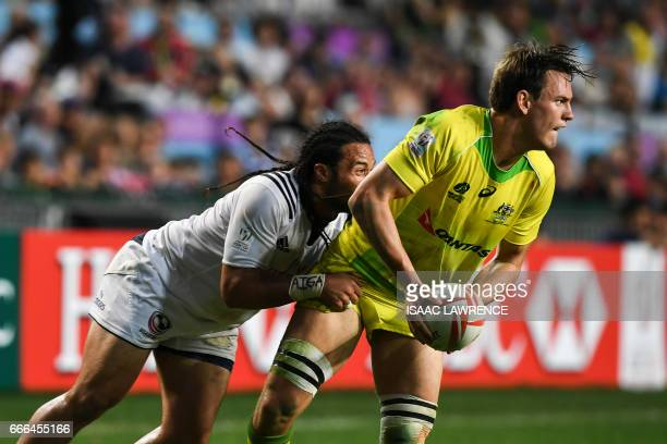 Lachie Anderson of Australia looks to pass the ball as Mike Te'o of the US makes a tackle during the bronze medal match on the third and final day of...