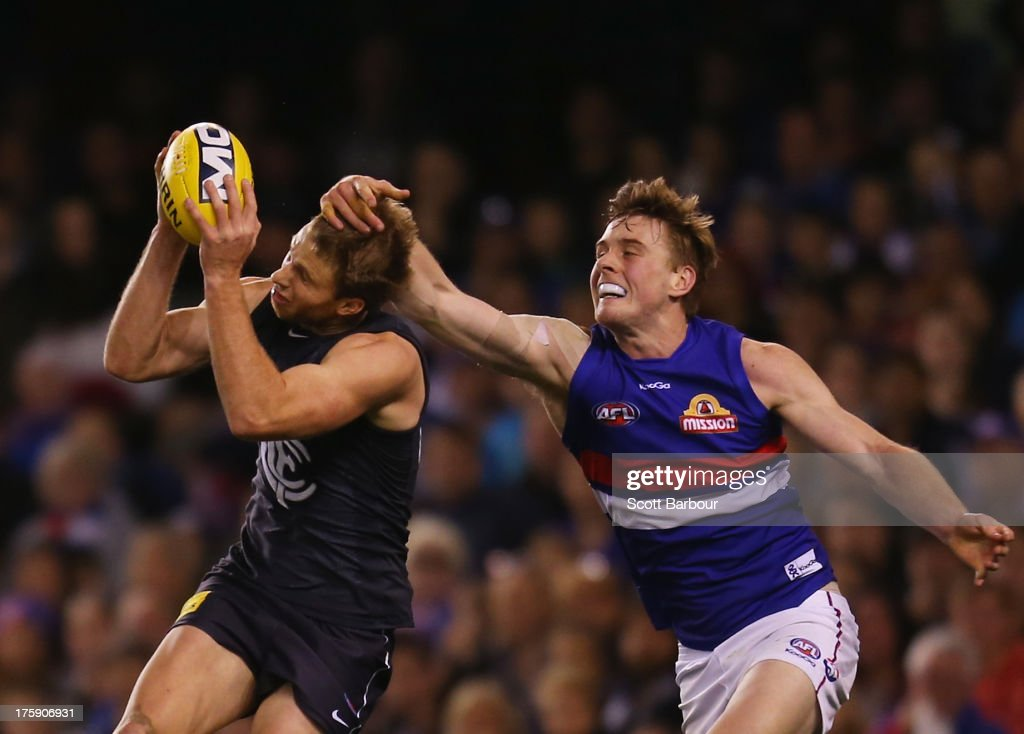 Lachie Henderson of the Blues marks the ball ahead of Jordan Roughead of the Bulldogs during the round 20 AFL match between the Carlton Blues and the Western Bulldogs at Etihad Stadium on August 10, 2013 in Melbourne, Australia.
