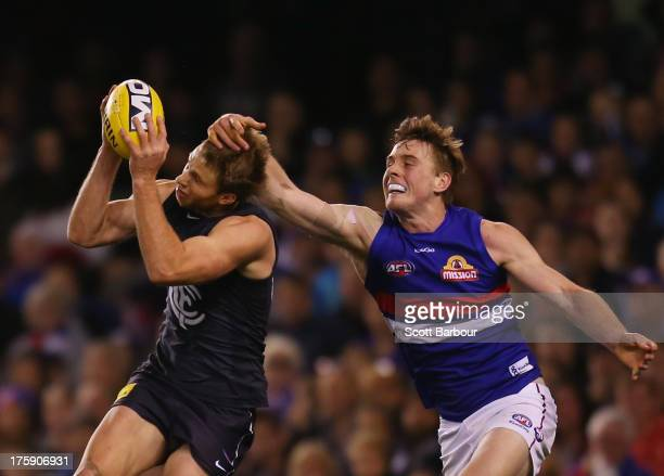 Lachie Henderson of the Blues marks the ball ahead of Jordan Roughead of the Bulldogs during the round 20 AFL match between the Carlton Blues and the...