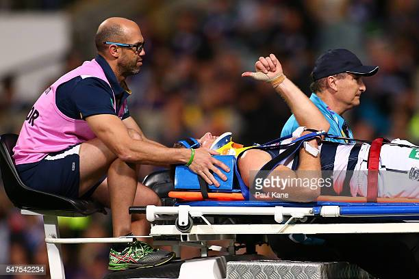 Lachie Henderson of the Cats acknowledges the crowd while being taken from the field on the mobile stretcher during the round 17 AFL match between...