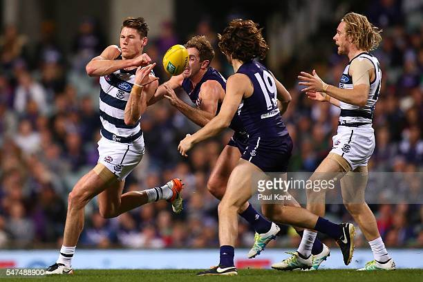 Lachie Henderson of the Cats handballs during the round 17 AFL match between the Fremantle Dockers and the Geelong Cats at Domain Stadium on July 15...