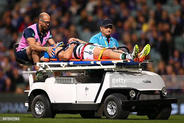 Lachie Henderson of the Cats is taken from the field on the mobile stretcher during the round 17 AFL match between the Fremantle Dockers and the...