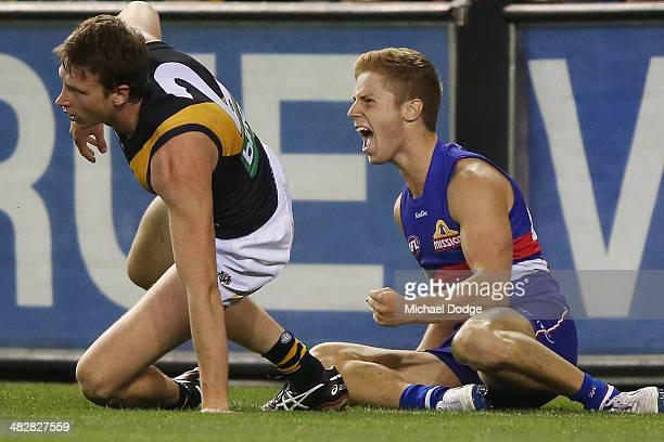 Lachie Hunter of the Bulldogs celebrates a goal next to Dylan Grimes of the Tigers during the round three AFL match between the Western Bulldogs and...