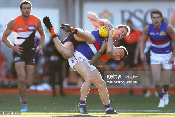 Lachie Hunter of the Bulldogs is challenged by Daniel Lloyd of the Giants during the AFL 2nd Elimination Final match between the Greater Western...