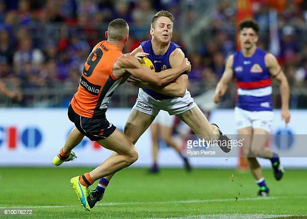 Lachie Hunter of the Bulldogs is tackled by Tom Scully of the Giants during the AFL First Preliminary Final match between the Greater Western Sydney...