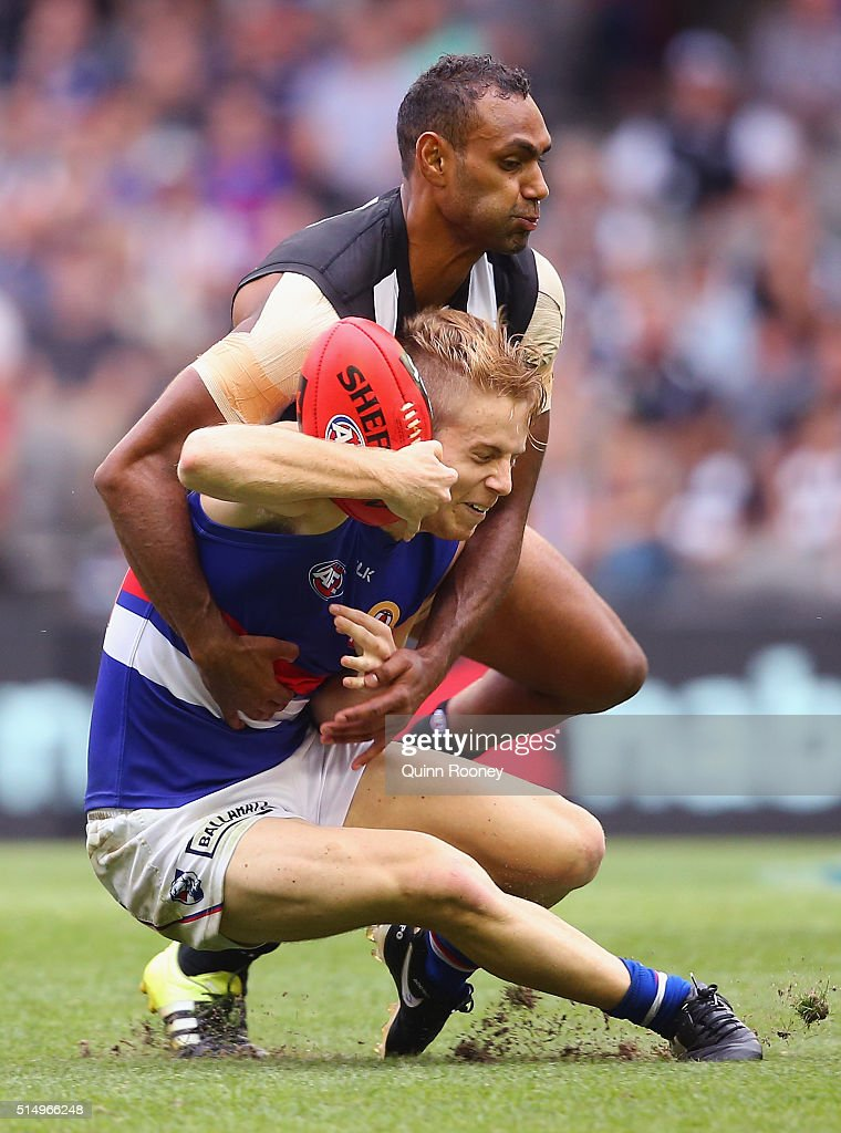 Lachie Hunter of the Bulldogs is tackled by Travis Varcoe of the Magpies during the 2016 NAB Challenge AFL match between the Collingwood Magpies and the Western Bulldogs at Etihad Stadium on March 12, 2016 in Melbourne, Australia.