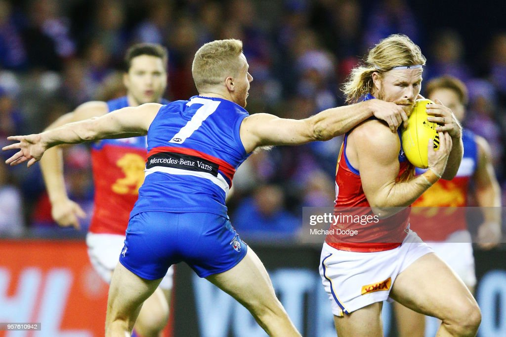 Lachie Hunter of the Bulldogs tackles Daniel Rich of the Lions during the round eight AFL match between the Western Bulldogs and the Brisbane Lions at Etihad Stadium on May 12, 2018 in Melbourne, Australia.