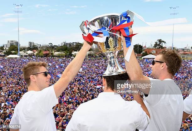 Lachie Hunter, Tom Liberatore and Jake Stringer of the Bulldogs show the trophy to the crowd during the Western Bulldogs AFL Grand Final celebrations...