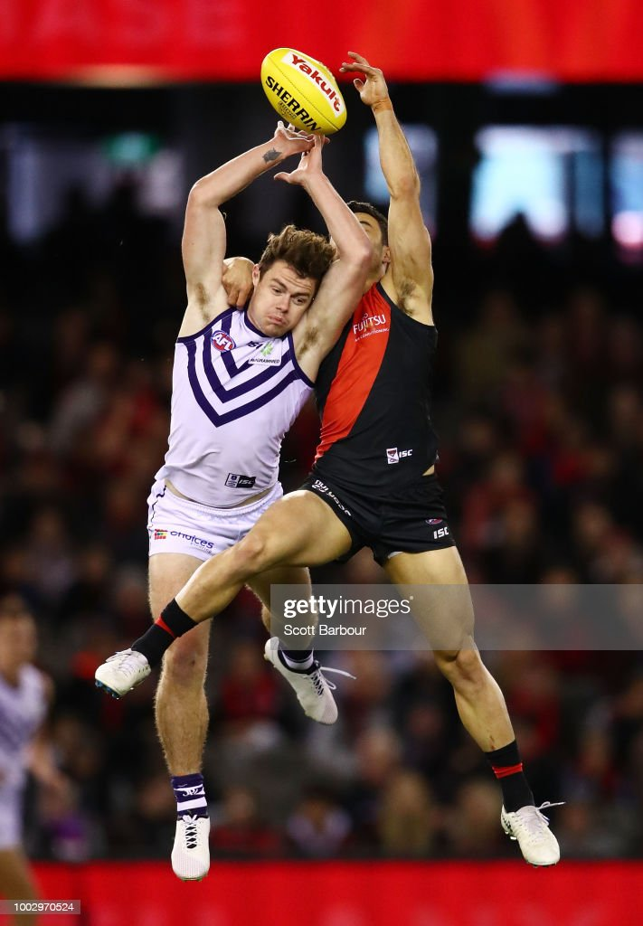 Lachie Neale of the Dockers and Ben McNiece of the Bombers compete for the ball during the round 18 AFL match between the Essendon Bombers and the Fremantle Dockers at Etihad Stadium on July 21, 2018 in Melbourne, Australia.