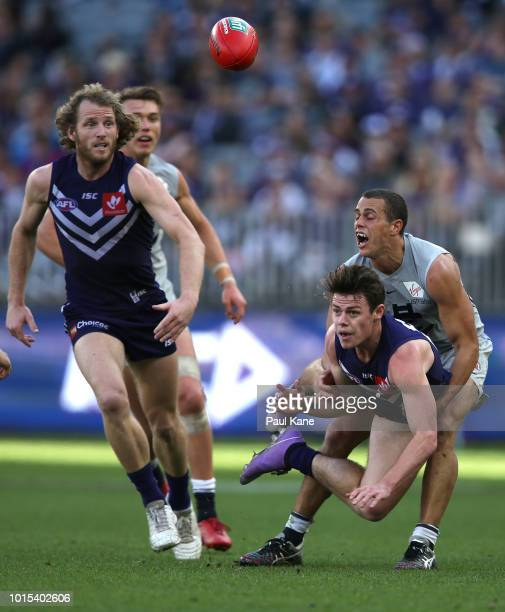 PERTH AUSTRALIA AUGUST Lachie Neale of the Dockers gets his handball away while being tackled by Ed Curnow of the Blues during the round 21 AFL match...