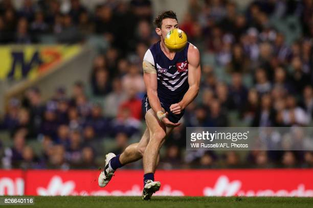 Lachie Neale of the Dockers handpasses the ball during the round 20 AFL match between the Fremantle Dockers and the Gold Coast Suns at Domain Stadium...