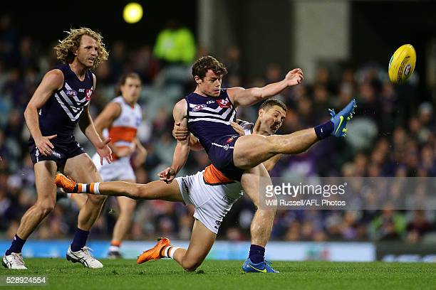 Lachie Neale of the Dockers kicks the ball under pressure from Josh Kelly of the Giants during the round seven AFL match between the Fremantle...