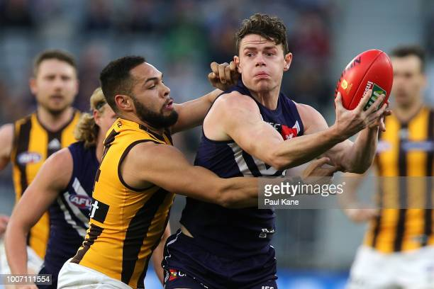 Lachie Neale of the Dockers looks to handball while being tackled by Jarman Impey of the Hawks during the round 19 AFL match between the Fremantle...