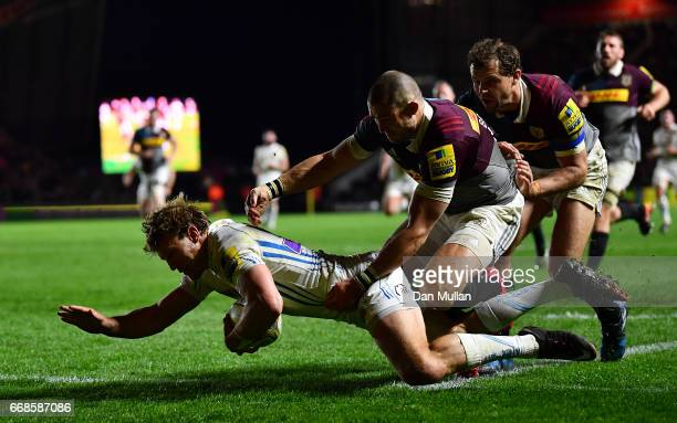 Lachie Turner of Exeter Chiefs dives over for a try under pressure from Mike Brown and Nick Evans of Harlequins during the Aviva Premiership match...
