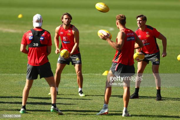 Lachie Weller and David Swallow handball during a Gold Coast Suns AFL training session at Metricon Stadium on July 27 2018 in Gold Coast Australia
