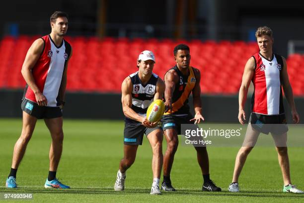 Lachie Weller handballs during a Gold Coast Suns AFL training session at Metricon Stadium on June 15 2018 in Gold Coast Australia
