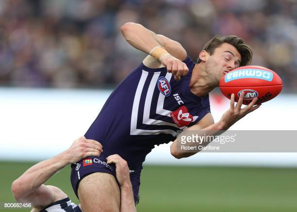 Lachie Weller of the Dockers handballs during the round 14 AFL match between the Geelong Cats and the Fremantle Dockers at Simonds Stadium on June 25...