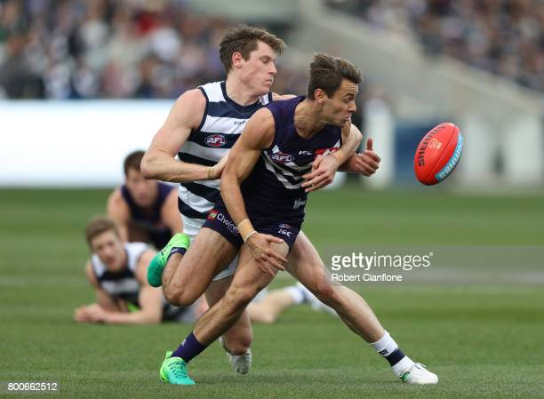 Lachie Weller of the Dockers is challenged by Rhys Stanley of the Cats during the round 14 AFL match between the Geelong Cats and the Fremantle...