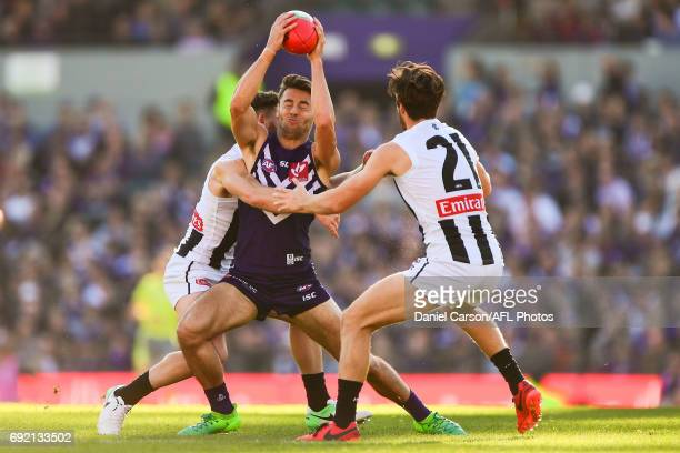 Lachie Weller of the Dockers is held up by Tom Phillips of the Magpies during the 2017 AFL round 11 match between the Fremantle Dockers and the...