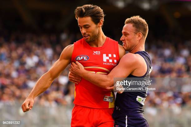 Lachie Weller of the Suns and Brandon Matera of the Dockers compete for the bvall at the boundary line during the 2018 AFL round 03 match between the...