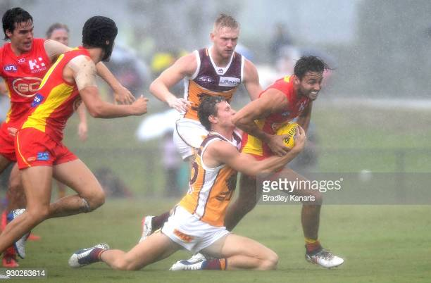 Lachie Weller of the Suns attempts to break away from the defence during the JLT Community Series AFL match between the Gold Coast Suns and the...