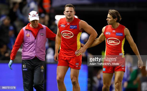Lachie Weller of the Suns chats to Steven May of the Suns as he leaves the field injured during the 2018 AFL round 16 match between the North...