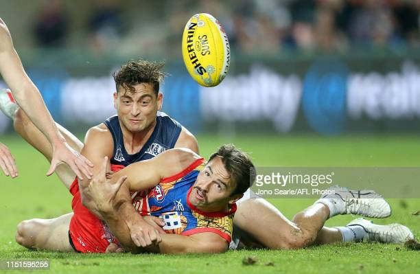 Lachie Weller of the Suns handballs during the round 10 AFL match between the Gold Coast Suns and the Geelong Cats at Metricon Stadium on May 25,...