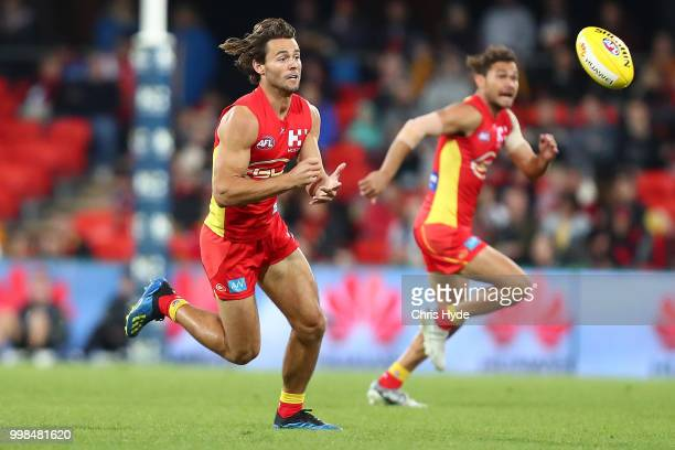 Lachie Weller of the Suns handballs during the round 17 AFL match between the Gold Coast Suns and the Essendon Bombers at Metricon Stadium on July 14...