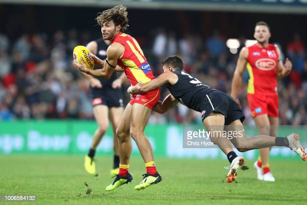 Lachie Weller of the Suns handballs during the round 19 AFL match between the Gold Coast Suns and the Carlton Blues at Metricon Stadium on July 28...